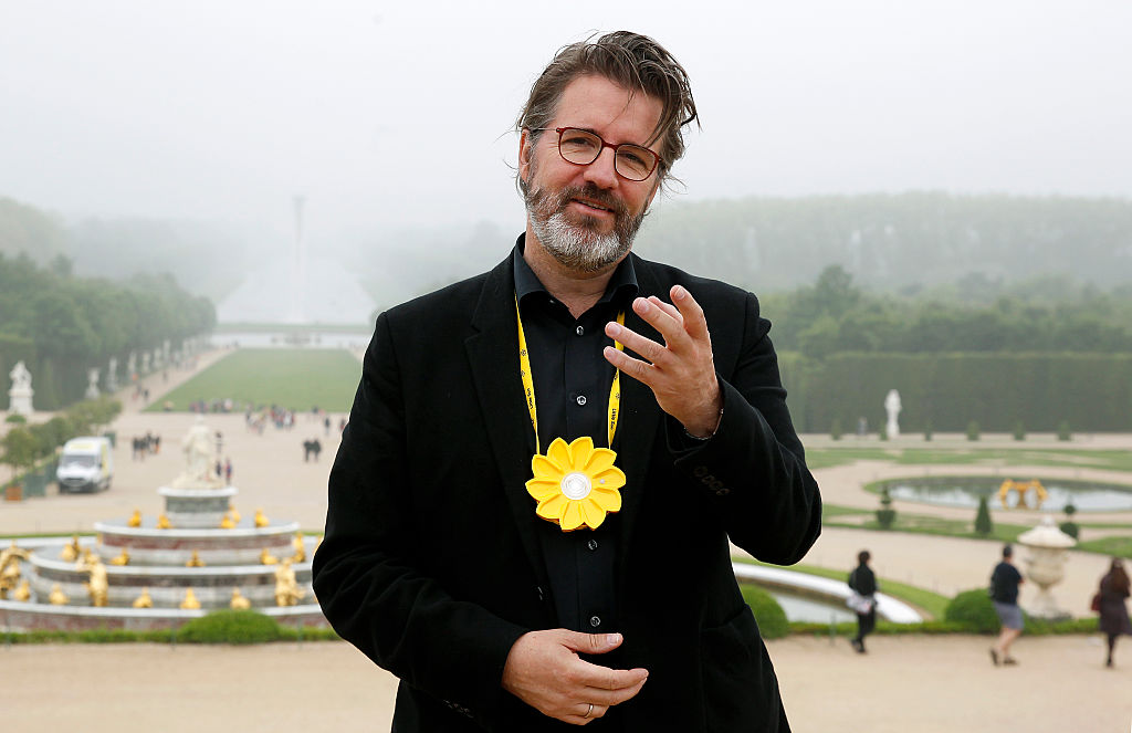 """Artist Olafur Eliasson poses in front of his artwork named """"Waterfall"""" at the opening of the exhibition of his works in the gardens of the Chateau de Versailles on June 6, 2016, in Versailles, France"""