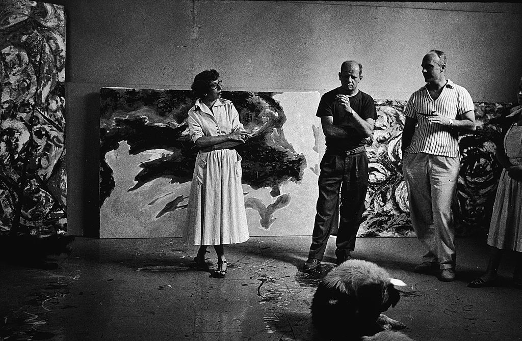 American abstract expressionist painter Jackson Pollock and his wife Lee Krasner and an unidentified couple stand around a dog and smoke in his studio at 'The Springs,' East Hampton, New York
