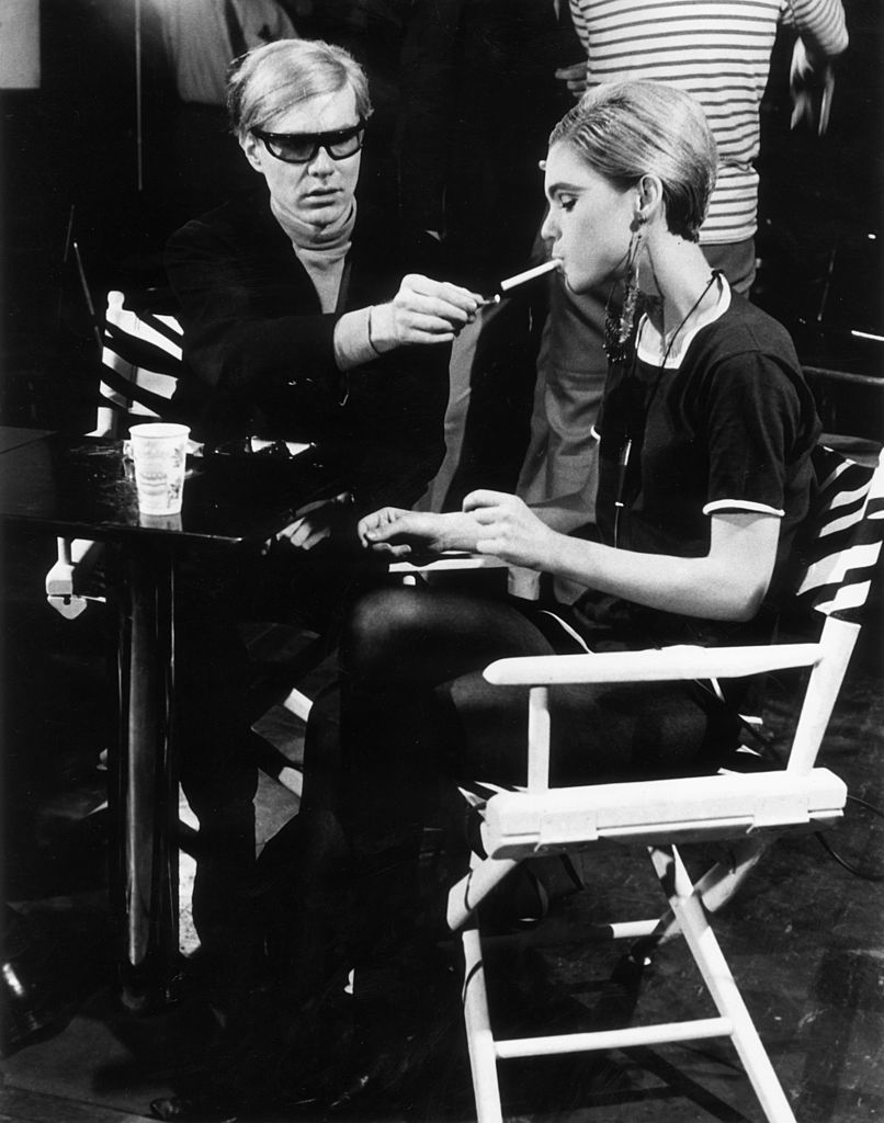American Pop artist Andy Warhol (1928 - 1987) sits next to actor Edie Sedgwick (1943 - 1971) and lights her cigarette, on the set of one of his films