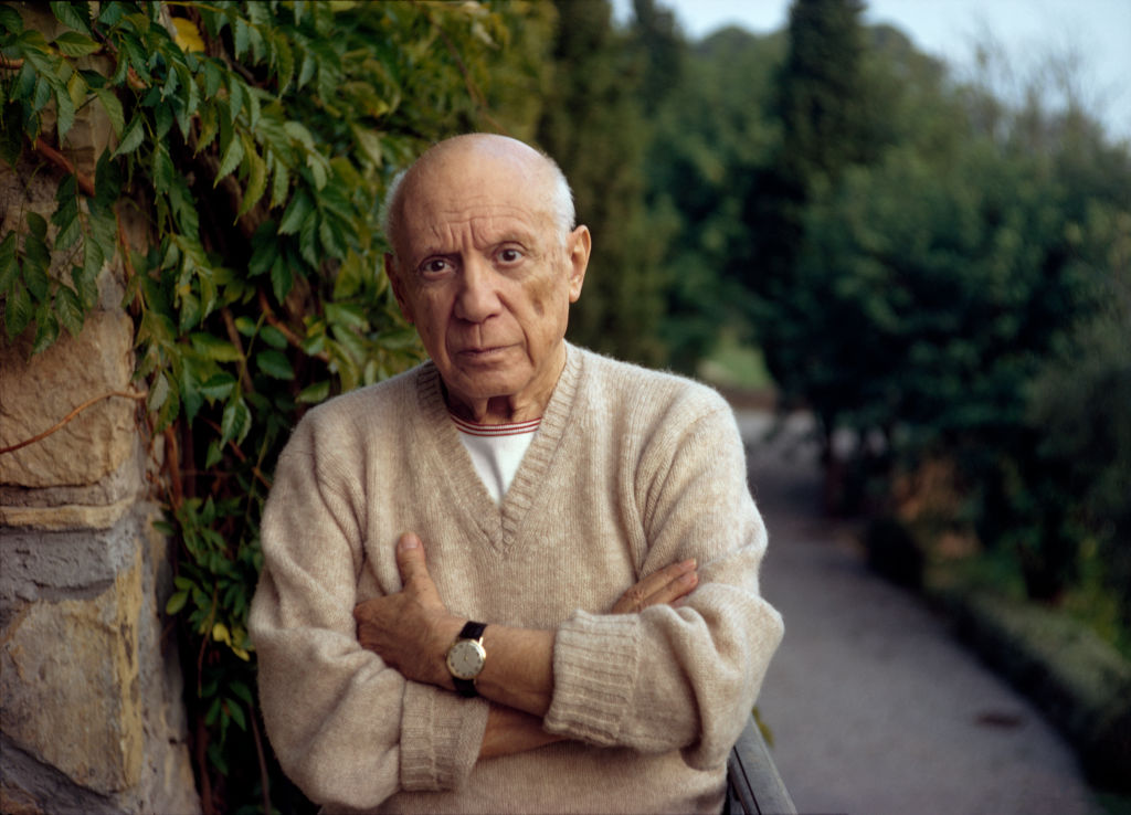Pablo Picasso standing by a green fern with folded arms, wearing a cashmere sweater